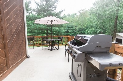 Patio - A patio wraps around the side and front of The Cottage, with a gas grill and a dining set.