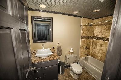 Bathroom 2 - Travertine shower, granite sink top and porcelain floor tile.