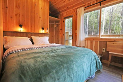 Maple Master  Hocking Hills Treehouse Cabins - The first floor master bedroom inside The Maple gives guests view of the gorge from two sides and includes two entryways to the wrap around deck and wood-fired hot tub  Hocking Hills Treehouse Cabins