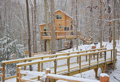 White Oak in Winter - The White Oak features its own access bridge - step into the magic of incredible views across the property from wrap around decks,  private balcony, or the wood-fired hot tub  Hocking Hills Treehouse Cabins