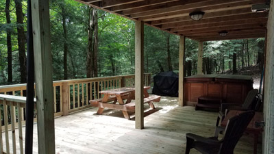 back deck - the back deck features a covered area with hot tub and seating, along with open air space with picnic table and grill.  this area is awesome, with wooded views on all sides