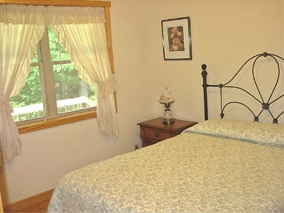 Bedroom East - This room offers a morning view of the sun, has a queen bed, two night stands and clothes hooks.
