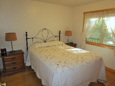 West Bedroom - This bedroom has a queen bed and two night stands, plus a closet.