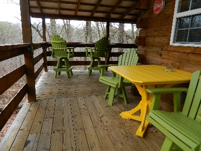 The Yesteryear - Side deck with table and chairs and a tiki bar overlooking the forest.