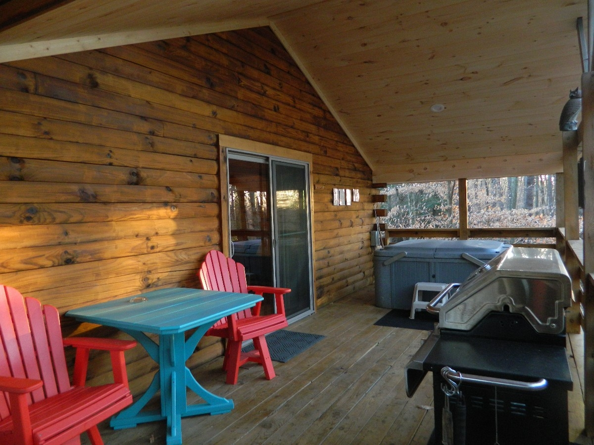 The Overlook - Back patio with hot tub, table and chairs with a gas grill overlooking the forest