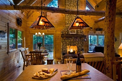 Photo 1412_2730.jpg - Full river rock fireplace and full hand-peeled logs throughout the cabin.  Main floor also features master bedroom with HDTV, full bathroom, and reclining leather sofas.