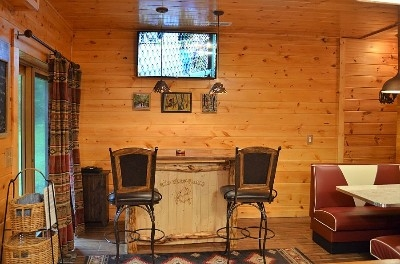 Photo 1412_4026.jpg - The Game Room offers fun and entertainment with a custom bar with walnut top and skip peeled cherry logs, a stove fireplace, infrared sauna, Diner Booth, Pool Table, Arcade Machine, HDTV, stereo, and more!