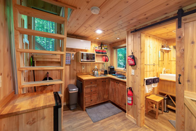 White Oak  Hocking Hills Treehouse Cabins - The kitchenette in The White Oak Treehouse includes a 2-burner electric cooktop, mini fridge, Keurig, toaster, electric griddle, crock pot, sink, microwave, cookware and dishes. There is also an outdoor grill and fire pit  Hocking Hills Treehouse Cabins.