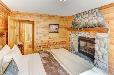 Waters Edge Bedroom - Bedroom with double sided glass fireplace. See more at Cherryridgeretreat.com