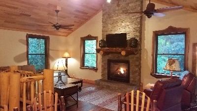 Great Room - A stone fireplace soars from floor to ceiling.  The gas log fireplace offers warmth and atmosphere.  Comfortable seating accents the area.