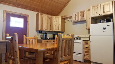 Dining/Kitchen - features log table and chair along with new hickory cabinets in kitchen.