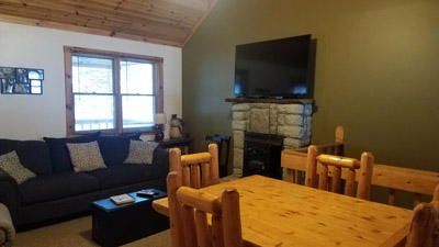 Living Room/Dining Room - Features a log dining table and chairs, large screen TV, fireplace