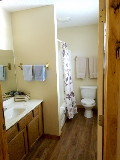 Cabin 1 - Bathroom - This full bathroom feather both a tub and shower with towels provided.