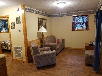 The Evergreen Cabin - living room - The quaint cabin features a separate bedroom and cozy living room with a sofa bed, DirectTv and new hardwood floors.