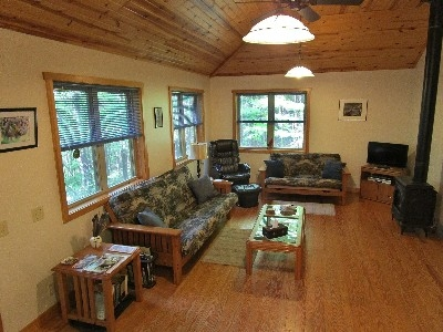 Photo 626_3783.jpg - Coffered pine ceiling, ceiling fan, pendant lights and lots of large windows with beautiful wooded views. The gas log fireplace is warm and charming and creates a relaxed atmosphere.