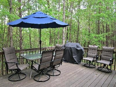 Deck area - The 14 foot high, 12x16 foot deck is complete with patio table and chairs, propane grill, bench, and lovely outdoor lamps for gentle night time illumination